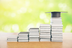 Knowledge concept. Creative book ladder with graduation cap on top. Green background. Knowledge concept. 3D Rendering Royalty Free Stock Images