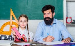 Knowledge day. Home schooling. private lesson. small girl child with bearded teacher man in classroom. daughter study royalty free stock image