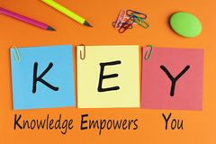 Knowledge Empowers You KEY Concept. Knowledge Empowers You words with KEY written on color notes with and office supplies. Business concept. Top view stock images