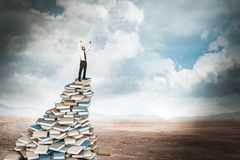 Knowledge is everything. Businessman on top of book stack stock images