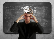 Knowledge and exams concept. Pensive young businessman with drawn mortarboard standing on concrete wall background with mathematical formulas on chalkboard Stock Image