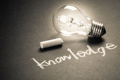 Knowledge. Handwriting of Knowledge word with chalk and glowing light bulb Royalty Free Stock Photo