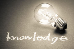 Knowledge. Handwriting of Knowledge word with glowing light bulb Stock Photography
