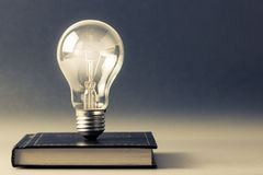 Knowledge. Light bulb glowing on a hardcover book stock images