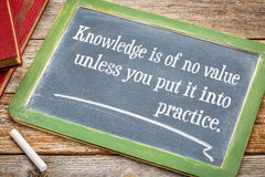 Knowledge is of no values unless you put it into practice. Motivational text on a slate blackboard with chalk and a stack of books against rustic wooden table stock photos