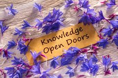 Knowledge Open Doors. In looking memo on white wood with beautiful blue flowers around Stock Images