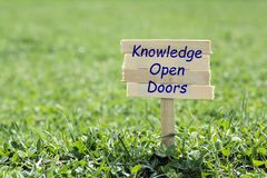 Knowledge open doors. Wooden sign in grass,blur background Royalty Free Stock Image