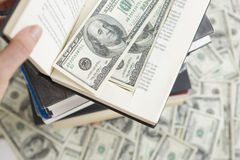 Knowledge opens opportunity. Prop book hiding one hundred dollar bills and bills as background Stock Photos