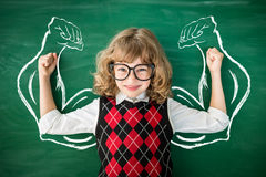 Knowledge is power concept. Strong child in class. Funny kid against green blackboard. Knowledge is power concept Royalty Free Stock Images