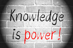 Knowledge is power. Graphic reading knowledge is power with exclamation point in black and red text on desaturated brick wall royalty free stock images