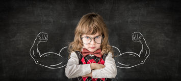 Knowledge is power. Strong child in class. Funny kid against blackboard. Education concept Royalty Free Stock Photos