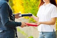Knowledge sharing between people. Close up outdoors of two students exchanging books. Knowledge sharing between people. Give books to read to a friend royalty free stock photography
