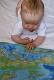 Knowledge of the world. The kid look the atlas of the world Royalty Free Stock Image