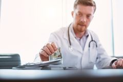 Knowledgeable doctor taking bribes in his office. My precious. Young bearded doctor sitting at the table and taking bribes royalty free stock photos