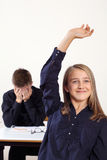 She knows the answer. Photo of two students in class, one with a raised hand to answer a question and the other frustrated stock image
