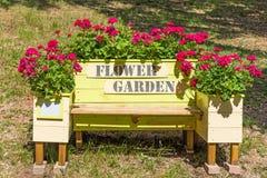 Künstlerische Gartenbank mit Pelargonienblumen Stockfoto