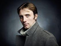 Künstlerisches dunkles Porträt des jungen schönen Mannes in einem grauen Mantel Stockbild