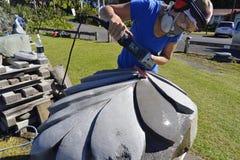 Künstlersteinbildhauer, der sculpting enormes Kunstwerk silbernen Farns Neuseelands schnitzt Stockfotos