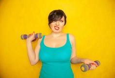 Knubbig glad emotionell flicka med kort hår i en blå t-skjorta som gör sportar med hantlar för att vara sunt och förlora vikt på  arkivbild