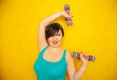 Knubbig glad emotionell flicka med kort hår i en blå t-skjorta som gör sportar med hantlar för att vara sunt och förlora vikt på  arkivbilder