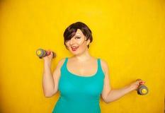 Knubbig glad emotionell flicka med kort hår i en blå t-skjorta som gör sportar med hantlar för att vara sunt och förlora vikt på  royaltyfri bild
