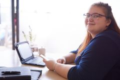 Knubbig kvinna som ser kameran, medan placerat i ett kafé arkivfoton