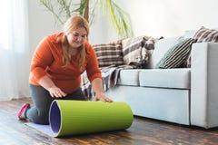 Knubbig kvinnasport hemma som sitter rullande mattt glat för yoga fotografering för bildbyråer