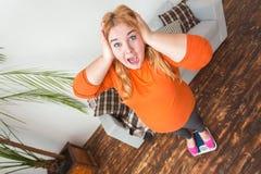 Knubbig kvinnasport hemma som står skrikig chockad bästa sikt för innehavhuvud royaltyfri fotografi