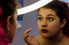 Knubbig sexig kvinna som sätter på någon makeup Arkivbilder