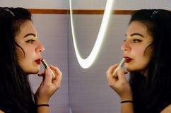 Knubbig sexig kvinna som sätter på någon makeup arkivfoto