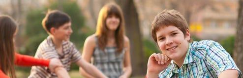 Knubbig tonårs- pojke som har gyckel med hans vänner i parkera på härlig höstdag Arkivfoto