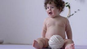 Knubbigt naket roligt barn med kakan i händer på fotoperiod i studionärbild arkivfilmer