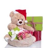 Knuddeliger Teddybär tragender Weihnachtshut und -Geschenkboxen auf Weiß Stockfotografie