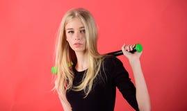 Knuppel van het de greephonkbal van het meisjes de tedere blonde op rode achtergrond Vrouw in honkbalsport Concept van de honkbal royalty-vrije stock fotografie