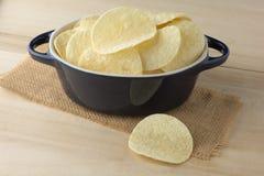 Knusperige Kartoffelchips in der dunkelblauen Schüssel Stockfoto