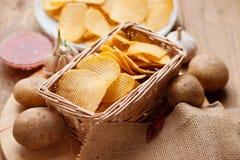Knusperige Kartoffelchips in einem Weidenkorb Stockbilder