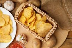 Knusperige Kartoffelchips in einem Weidenkorb Stockfoto