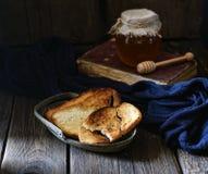 Knusperige Toast in der Weinleseplatte, -honig und -buch auf einem hölzernen Hintergrund Stockfoto
