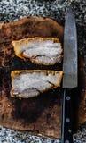 Knusperiges Schweinefleisch auf Holzklotz und Messer Lizenzfreie Stockfotos