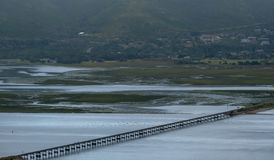 Knysna, South Africa: water in the estuary at Knysna Lagoon, with bridge carrying train lines running across the water. The Garden Route, South Africa: water in royalty free stock image