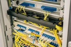 Knyta kontakt kablar förbindelse till strömbrytareportar i datacenterskåp, rengöringsduk eller cell- servermaskinvaruutrustning arkivbild