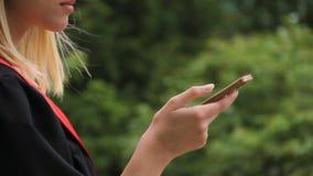 Knyter kontakt doktorand- bläddra nyheterna för kvinnlign i samkväm på smartphonen, avläggande av examen lager videofilmer