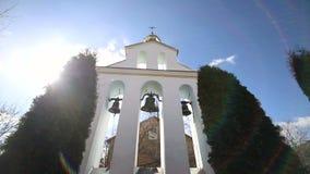 Kościelni dzwony na słonecznym dniu w silnym wiatrze Wiatr trząść drzewa blisko dzwonkowy wierza i Sonechka błyszczy w zbiory
