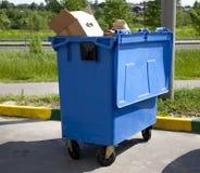 Kołowego kosza błękitny plastikowy grat ja na chodniczku przy gazonem fo Zdjęcia Stock