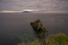 Kołysa przy przylądkiem i wyspą w morzu na horyzoncie Obraz Royalty Free