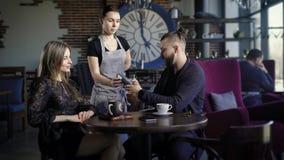 Końcówka gość restauracji w eleganckiej kawiarni Facet i dziewczyna przygotowywamy płacić mężczyzna uses kredytowa karta kelner p zdjęcie wideo
