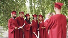 Kończyć studia ucznia jest magnetofonowym wideo jego przyjaciele trzyma dyplomy w togach, machający ręki i pozować patrzeć zbiory wideo