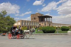 Końska fura z ludźmi przy Naqsh-e Jahan kwadratem lub Iman kwadratem z sławnym Ali Qapu pałac w tle , w Isfahan, Ja zdjęcie royalty free