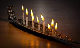 Kościelne świeczki w srebnym kandelabrze z postacią Buddha Zdjęcia Royalty Free