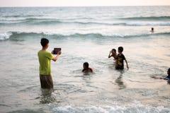 KO张,泰国- 2018年4月10日:使用在海男孩的塔伊亚裔孩子通过片剂拍照片 免版税库存图片